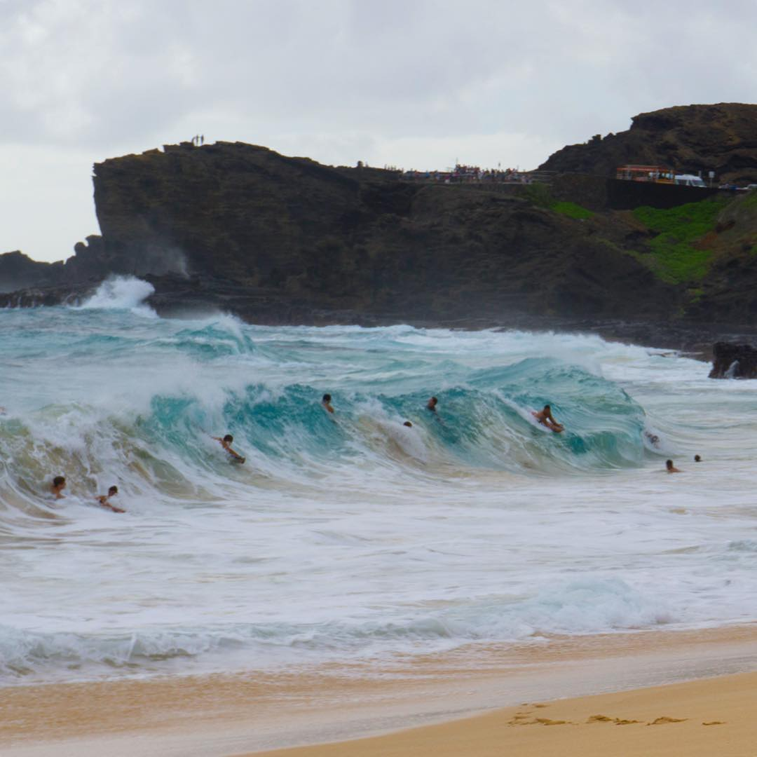 body surfers and boogie boarders riding the crazy sandy beach shore break